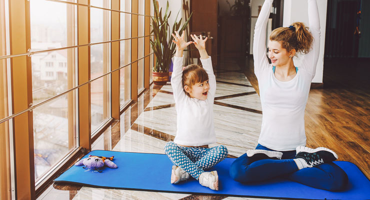 Madre e hija practicando yoga en casa